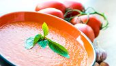 A bowl of tomato soup gaspacho with basil, tomatoes and garlic