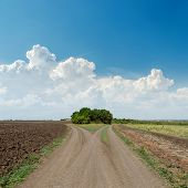two rural roads to horizon and clouds in blue sky