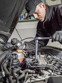 Auto mechanic replacing glow plugs in car diesel engine using spark plug spanner