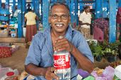 HIKKADUWA, SRI LANKA - FEBRUARY 23, 2014: Portrait of vendor with water bottle. The Sunday market is great way to see Hikkaduwa's local life come alive along with fresh produce and local delicacy