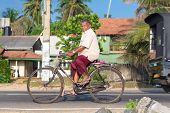HIKKADUWA, SRI LANKA - FEBRUARY 24, 2014: Elderly man in sarong and shirt riding a bicycle. Cycling is the main transportation for the traditional people in the country.