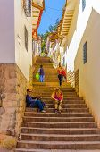 CUSCO, PERU, MAY 1, 2014 - Couple of tourists rests on stairs in narrow alley