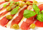 Thin slices of prosciutto crudo and marinated green olives