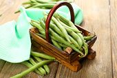 French beans in wooden basket on table close-up