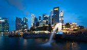 SINGAPORE - 1 JAN, 2014: Marina Bay central business district in Singapore. Late evening panorama of popular tourist area in downtown of city. Merlion statue in the front is the symbol of Singapore