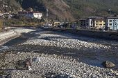 Two Men Clean The Riverbed In Paro, Bhutan