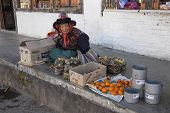 A Woman Sells Food On The Sidewalk Of The Main Street Of Paro, Bhutan