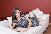 stock photo of futon  - Beautiful young elegant girl wearing grey dress lying on the white sofa - JPG