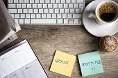 stock photo of morning  - Digital tablet computer with sticky note paper and cup of coffee on old wooden desk - JPG