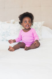 picture of babygro  - Baby girl in pink babygro sitting on bed at home in the bedroom - JPG