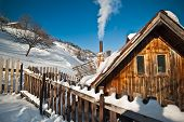 Old wooden cottage with hill covered by snow in background. Bright cold winter day in the mountains