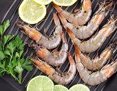 Raw shrimps on pan with lemon.
