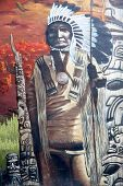 MONTREAL CANADA AUGUST 21 2014: Street art and graffiti. Exterior portrait of a Native American chief with spear, with totem poles in the background.