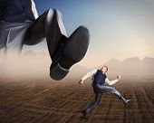 stock photo of big-foot  - Businessman runs from a big foot - JPG