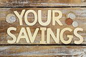Your savings written with wooden letters on rustic surface