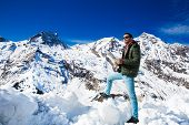 Tourist on the background of snowy mountains