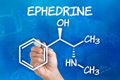 Hand with pen drawing the chemical formula of ephedrine