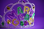 A colorful mardi gras crown on a purple background