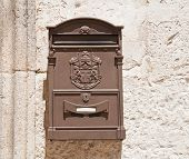 Brown Post box on wall.
