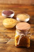 Dijon Mustard in glass jar  and mustard seeds and sauce in bowls on wooden background