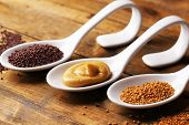 Mustard seeds, powder and sauce in spoons on wooden background