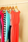 Female dresses on hangers in room