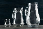 Glass jugs on dark color wooden background