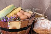 Wooden basket with flowers, maize and eggs on sacking background