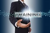 Businessman hand showing training button.