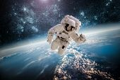 stock photo of space stars  - Astronaut in outer space against the backdrop of the planet earth - JPG