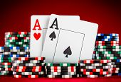 Stack of chips and two aces on the table on the red baize - poker game concept