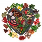 Herb and spice ingredients on a heart shaped slate and loose over white background.