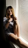 picture of louvers  - Beautiful girl near the window closed louver on a sunny day - JPG