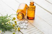 stock photo of chamomile  - Chamomile and bottle with pills on white table - JPG