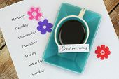 Good morning card with cup of tea and days of the week listed on white paper
