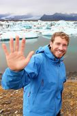 Tourist waving hand by Jokulsarlon on Iceland on travel. Portrait of happy man saying hello smiling looking at camera front of the glacial lake / glacier lagoon.