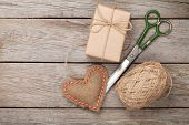 Valentines day gift wrapping with boxes and scissors over white wooden table