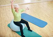 Active Senior Woman At Gym Exercising With Weights