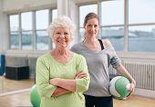 Senior Woman At Health Club With Gym Instructor