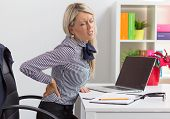 foto of stiff  - Young woman having back pain while sitting at desk in office - JPG