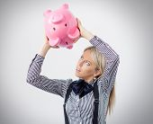 Woman trying to get some money out of piggy bank