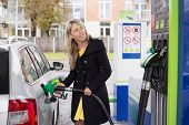 Woman refilling car with fuel