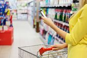 Woman checking shopping list on her smartphone