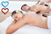 Attractive couple enjoying hot stone massage poolside against hearts