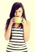 Young woman drinking something hot from big mug
