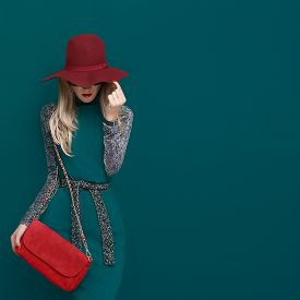 image of green snake  - Lovely blond model in fashionable red hat and a red clutch on green background - JPG