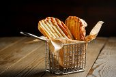 foto of crust  - Toasted slices of bread with a golden crust neatly stacked in a metal stand on a wooden brown background - JPG