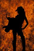 stock photo of western saddle  - A silhouette of a woman with a fire background holding on to her saddle - JPG