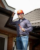 foto of handyman  - Portrait of handyman standing on high ladder and inspecting house roof - JPG