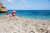 stock photo of children beach  - Girl buried in beach pebbles smiling and enjoying free time on the beach dressed in wetsuit and a hat for sun protection - JPG